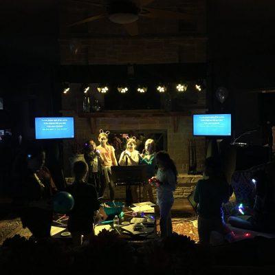 People having fun singing karaoke in front of two displays